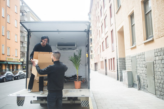 Male and female movers unloading box from truck on street in city