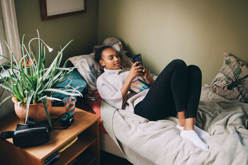 Female teenager using mobile phone while lying on bed at home