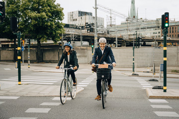 Smiling businessman and businesswoman riding bicycles on road in city Papier Peint