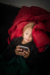 Overhead view of girl using mobile phone while relaxing in tent