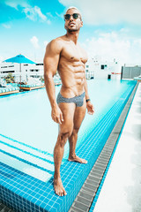 Handsome muscle guy in speedos at pool