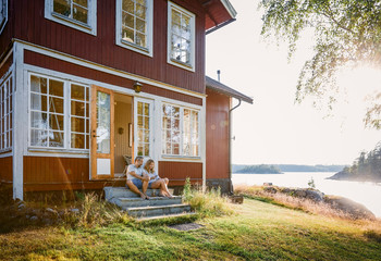 Full length of couple sitting at log cabin entrance by lake during summer