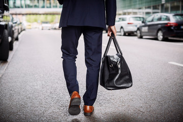 Low section of male lawyer carrying bag while walking on street