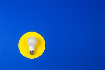 One light lamp bulb on yellow and navy blue background