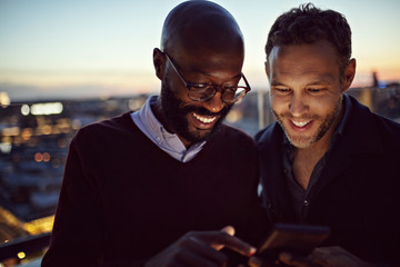 Smiling businessmen using mobile phone while standing on terrace during sunset