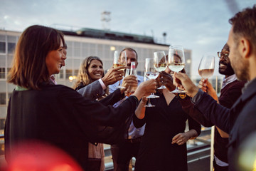 Business colleagues toasting wineglasses while celebrating office party on terrace