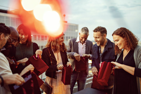 Happy business colleagues checking gift bags while enjoying office party on terrace