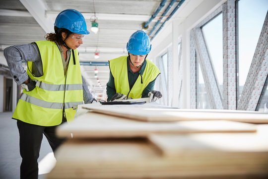Architects talking over blueprint at construction site