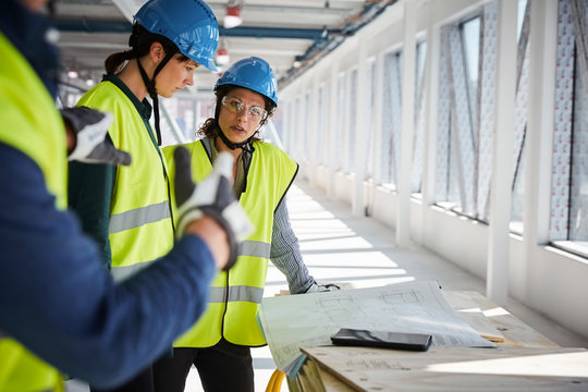 Female and male engineers discussing over blueprints at construction site