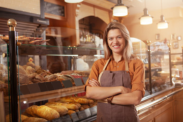 Foto op Canvas Bakkerij Happy mature small bakery owner smiling proudly at her confectionery store. Cheerful female baker working at her shop