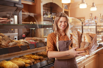 Zelfklevend Fotobehang Bakkerij Happy mature female baker holding basket of bread, working at her bakery store. Middle aged female entrepreneur selling homemade bread