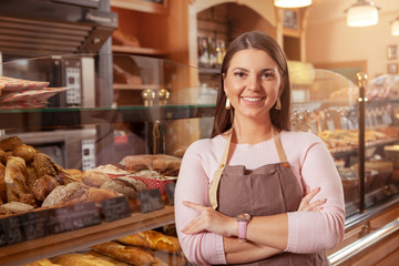 Cheerful female entrepreneur smiling confidently to the camera, working at her bakery store