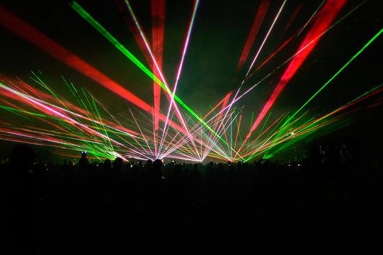 People bathed in fog and laser light, laser show.