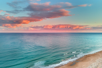 Fototapeten Lachs Picturesque scenery aerial drone point view landscape, calm blue Mediterranean Sea colourful fluffy glowing pink clouds at sunset evening sky, sandy coastline. La Mata, Torrevieja, Costa Blanca, Spain