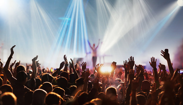 crowd with raised hands at concert festival banner