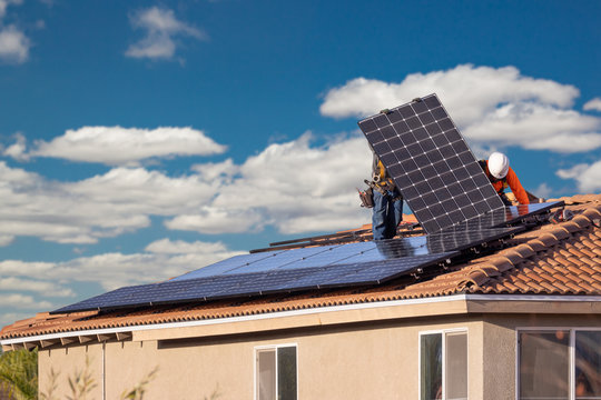 Workers Installing Solar Panels on House Roof