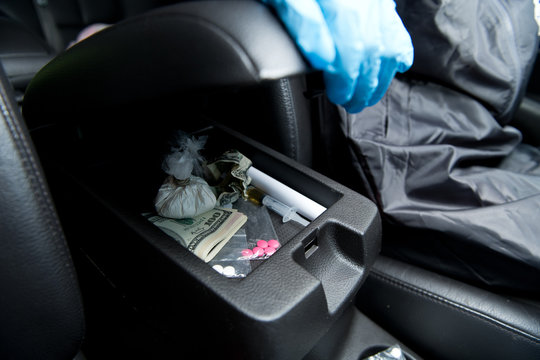policeman opens the glove compartment of a car in which drugs lie