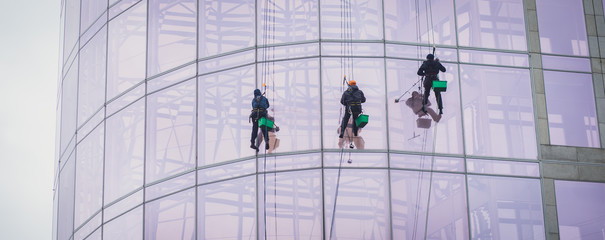 Group of workers cleaning the windows on the high rise building, industrial mountaineers washing the glass facade of a modern office building