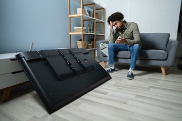 Man Sitting On Sofa In Front Fallen Television