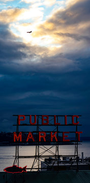 PIKE PLACE MARKET SUNSET VIEW OF PUGET SOUND WATERS ABD ALKI BEACH WITH JET AIRCRAFT SILHOUETTED IN SUNLIT CLOUDY SKY