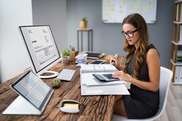 Accountant Calculating Tax At Desk Fotobehang