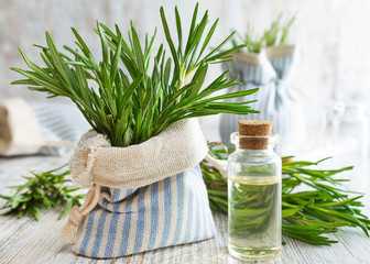 Rosemary essential oil and fresh rosemary in decorative pouch on old wooden table.
