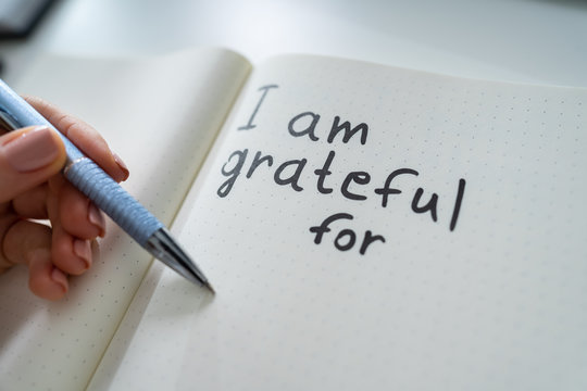 Person Writing I Am Grateful For Text