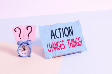 Conceptual hand writing showing Action Changes Things. Concept meaning start doing something against problem resolve or achieve it Alarm clock beside a Paper sheet placed on pastel backdrop