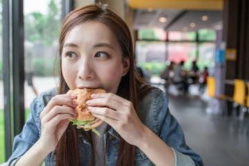 Pretty young woman eating hamburger Fototapete