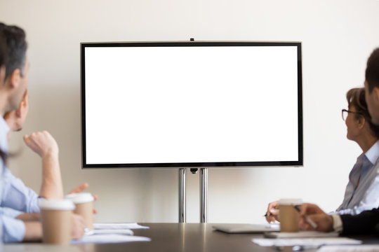 Businesspeople sitting in boardroom looking at tv with white blank