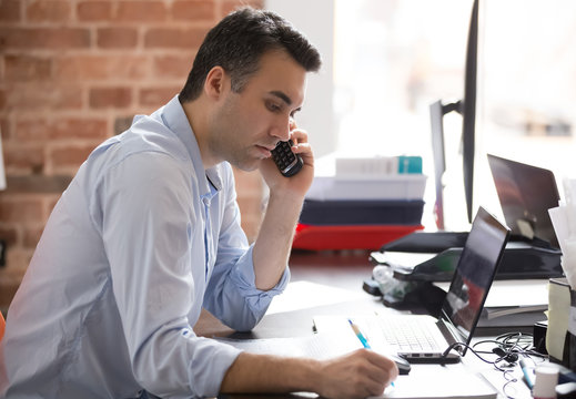 Serious businessman talking on phone having busy working day