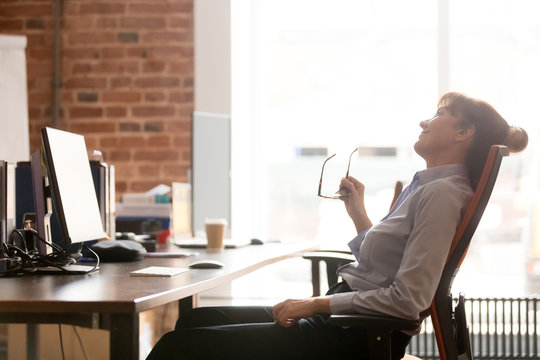 Side view relaxed businesswoman resting leaning on comfortable office chair