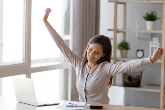 Smiling young woman stretching working at laptop