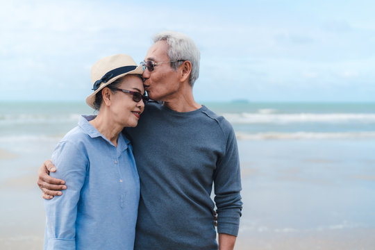 Kissing moment of asian couple senior elder retirement resting at beach honeymoon family together happiness people lifestyle, copy space the right