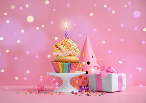Composition with birthday cupcake on pink background. Bokeh effect