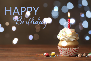 Delicious cupcake with candle on wooden table against blurred lights. Happy Birthday