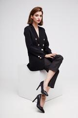 High fashion portrait of young elegant woman. Black jacket, pants.
