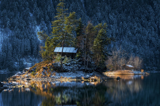 Evening light at the eibsee near grainau at the mountain zugspitze, reflection of island Braxeninsel in the winter at sunset