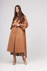 Young elegant woman in trendy brown coat.
