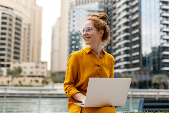 Young Woman sitting in Dubai Marina aria and work on laptop. Student or  freelancer lifestyle.
