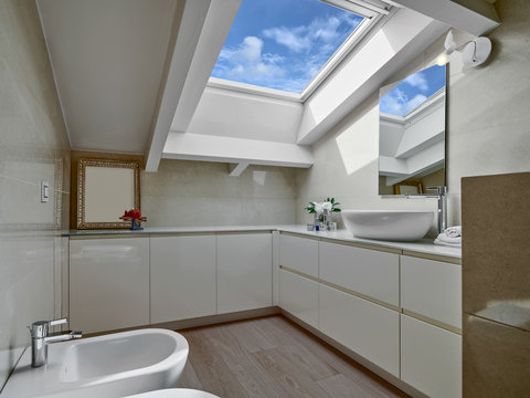 inteior shot of a modern bathroom in the attic with wood floor and the skylight