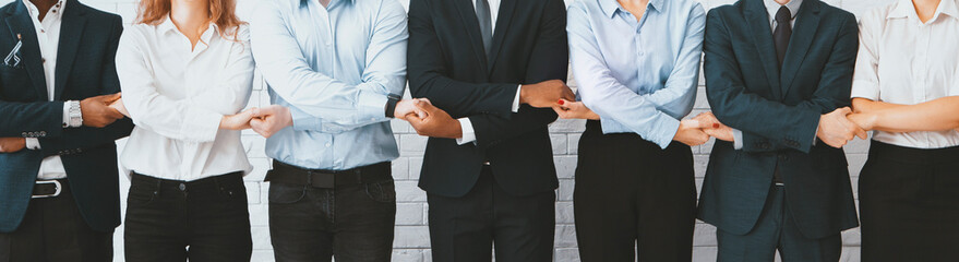 Business team holding hands, standing in row