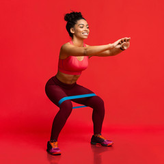 Young woman doing stretching work out with elastic bands