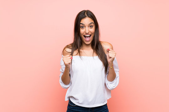 Young woman over isolated pink background celebrating a victory in winner position