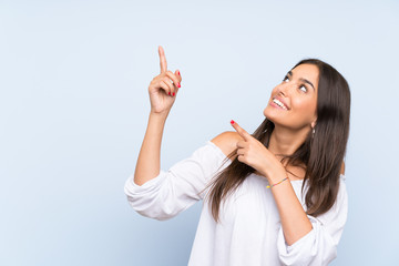 Young woman over isolated blue background pointing with the index finger a great idea