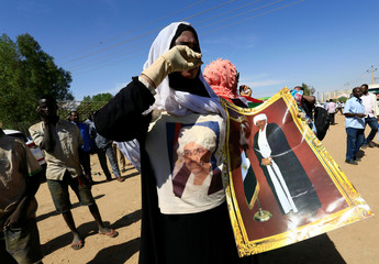A supporter of Sudanese former president Omar Hassan al-Bashir carries his picture during a protest outside the court house that convicted him on corruption charges in Khartoum