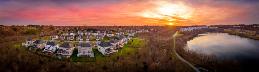 Aerial sunset panorama view of luxury upscale residential neighborhood gated community single family homes with decks and gazebos manicured green lawn lake view East Coast USA, American real estate  Fotomurales