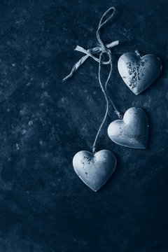 Love Valentines day greeting card with three silver hearts on rope cord over old dark metal background. Top view, copy space. Color of the year 2020 classic blue toned