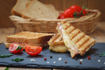 Club or toast sandwiches on black tray. Grilled sandwiches with ham salami, tomato and melted cheese.