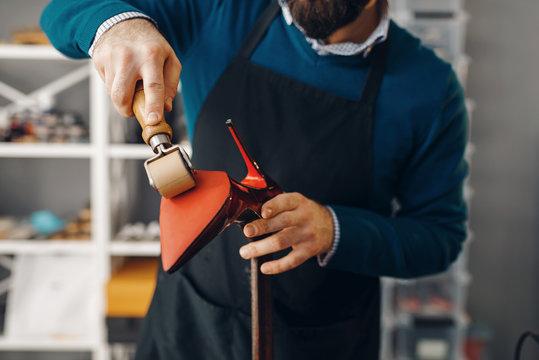 Shoemaker repairing shoe, footwear repair service